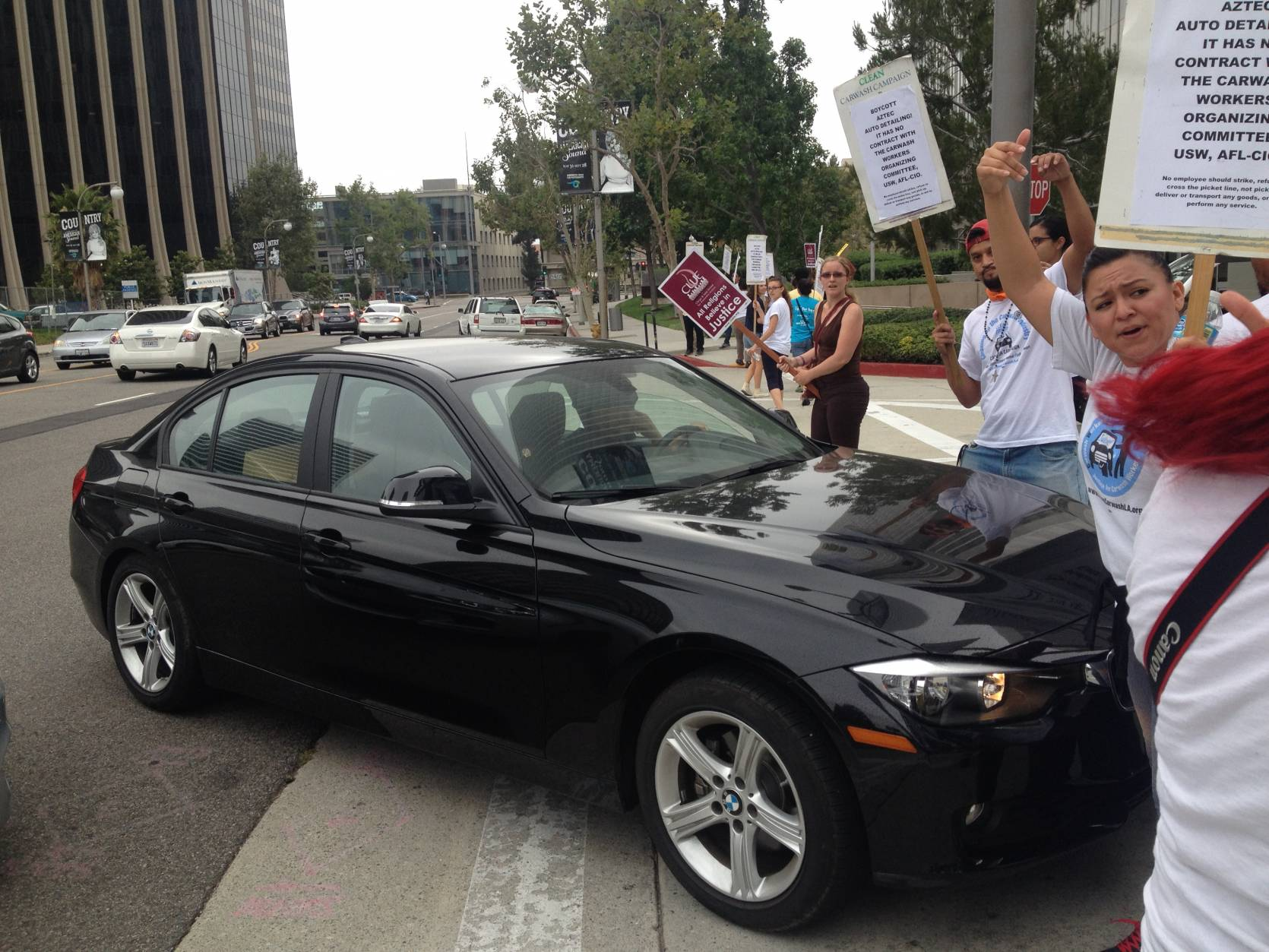 Hostile luxury car driver tries to drive through picket line