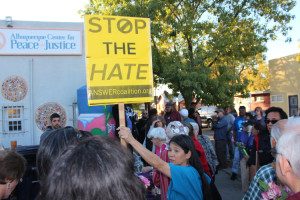 image - abq peace walk to islamic center - crowd woman with answer sign