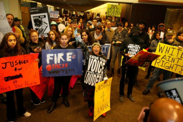 Protesters pause to rally during march through county building. Photo: Mercury News