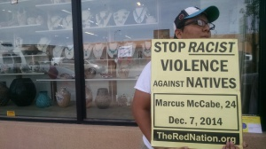 Protestor stands in front of store on Rt. 66 that buys Native jewelry and art for a pittance to turn around and sell for high profits to tourists.