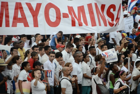 Under rain, hundreds of thousands of people in Havana marched to celebrate May Day. Marching with the large MINSAP (Ministry of Public Health) banner are doctors and nurses, including the Cuban medical workers who treated Ebola patients in West Africa.
