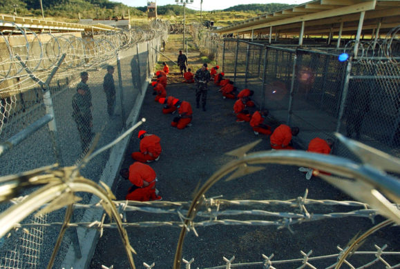 Detainees in orange jumpsuits sit in a holding area under the watchful eyes of Military Police at Camp X-Ray at Naval Base Guantánamo Bay, Cuba, during in-processing to the temporary detention facility on January 11, 2002.