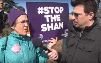 Pro-choice-abortion-supporter-at-rally-with-Stop-the-Sham-sign