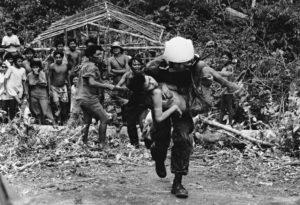 Piloto de helicóptero da Força Aérea Brasileira removendo mulher Yanomami adoentada. Ela foi transportada da maloca Hemosh, no Alto Rio Mucajaí para o posto médico de Surucucus.