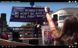 "Screen shot from ""History Made"" video showing WORD banner and Peta Lindsay (on right under banner)"