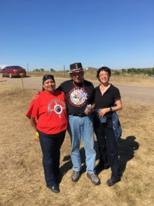 Gloria La Riva (right) and Dennis Banks (center) at Standing Rock earlier this year.