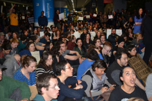 Crowd sitting at SFO. Liberation Photo: Gloria La Riva