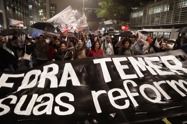 Demonstrators march carrying a banner that reads in Portuguese