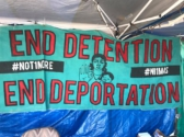 Banner in the encampment outside NWDC, photo: NWDC Resistance