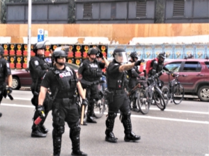 Seattle police brandish pepper spray canisters, Aug. 13, Seattle.