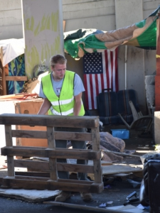 Seattle City worker breaks apart structures made by encampment residents.