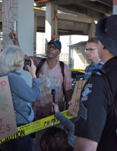 Homeless camp resident and activists argue with police.