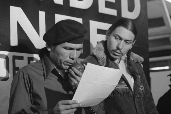Dennis Banks during 1973 Wounded Knee stand-off, AP photo by Jim Mone. Banks on left, Carter Camp, right.