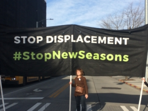 Banner opposing New Seasons at 23rd and Union along the MLK Day March route. Liberation Photo: Jane Cutter