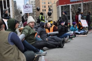 Protesters chained themselves together with metal pipes, symbolic of youth incarceration in Seattle. Liberation photo: Lee Hessler