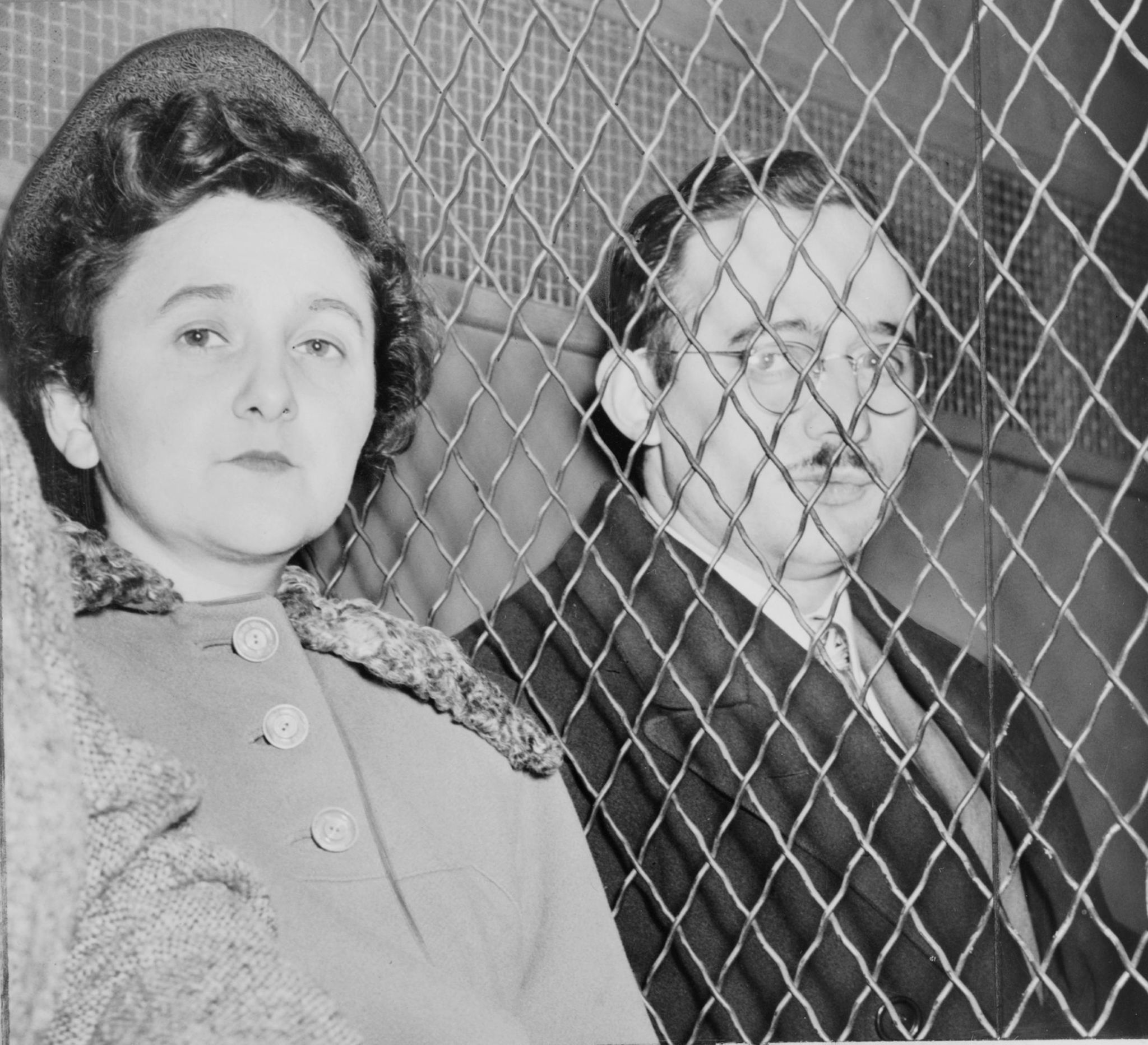 "Julius and Ethel Rosenberg, separated by heavy wire screen as they leave U.S. Court House after being found guilty by jury. Photo by Roger Higgins, photographer from ""New York World-Telegram and the Sun"" [Public domain], via Wikimedia Commons"