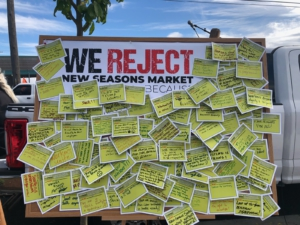 Cards detailing the reasons why workers and neighborhood residents reject New Seasons cover the speakers podium. Liberation photo.