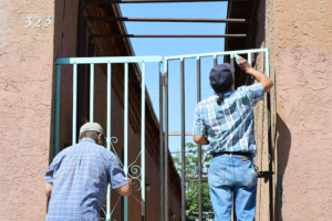 Two men paint the gate in front of the home of one of the last remaining residents of Duranguit. Liberation photo.