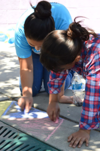 Two young girls decorating Duranguito sidewalk with chalk. Liberation photo.