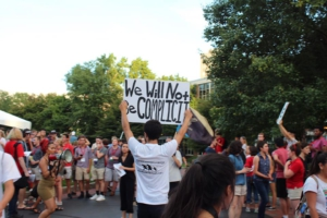 "Cosecha activist with sign ""We Will Not be Complicit"" Photo credit: Cosecha Boston"