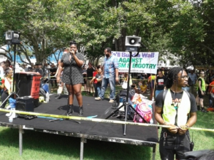 Counter-protest rally stage at Lafayette Park. Co-MC Kerbie Joseph of PSL at mic. Liberation photo by Paul Wilcox.