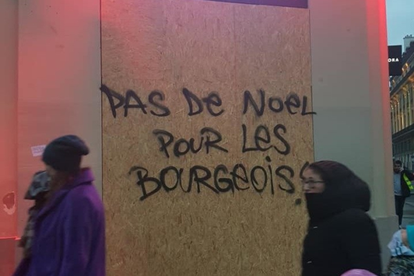 Graffiti on a boarded-up store during a Yellow Vests protest reads