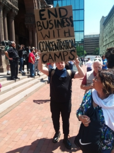 "A protestor holds a sign that reads ""end business with concentration camps"""