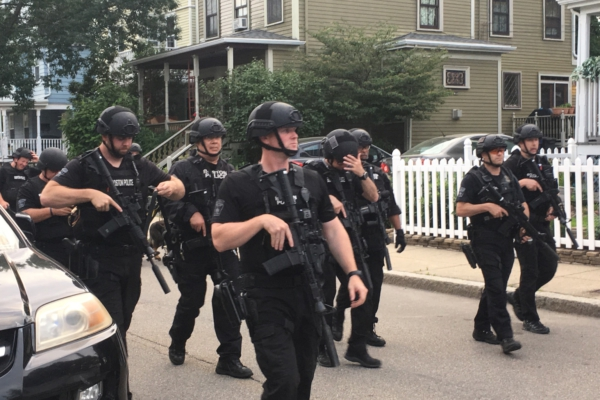 Boston Police officers walk through residential neighborhood in Dorchester carrying large guns