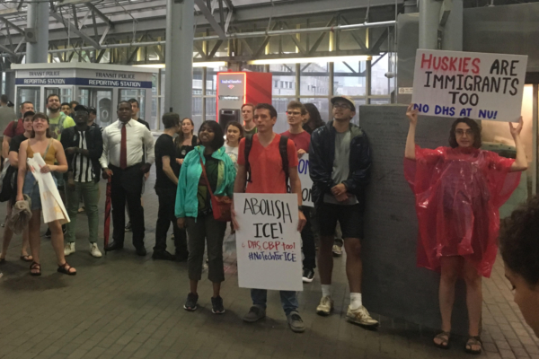 Students rally against DHS and ICE in Boston, holding signs