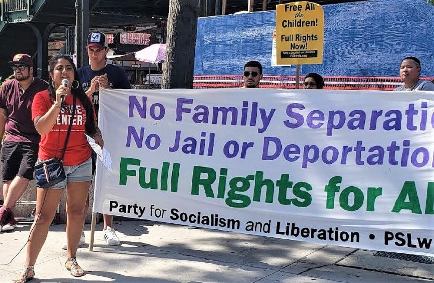 """Liberation photo. Activists hold a banner reading: """"No family separation! No jail or deportation! Full Rights for All! Party for Socialilsm and Liberation. A woman holds a microphone."""