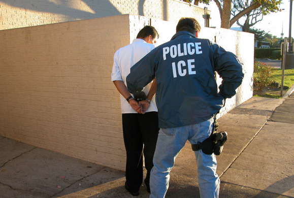 Armed ICE officer arrests man in white shirt and black pants.