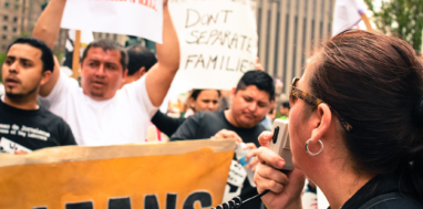 "Immigrant workers hold signs and banners while a person stands in foreground holding a microphone. One sign reads ""Don't separate families."""