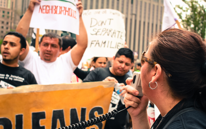 Immigrant workers hold signs and banners while a person stands in foreground holding a microphone. One sign reads