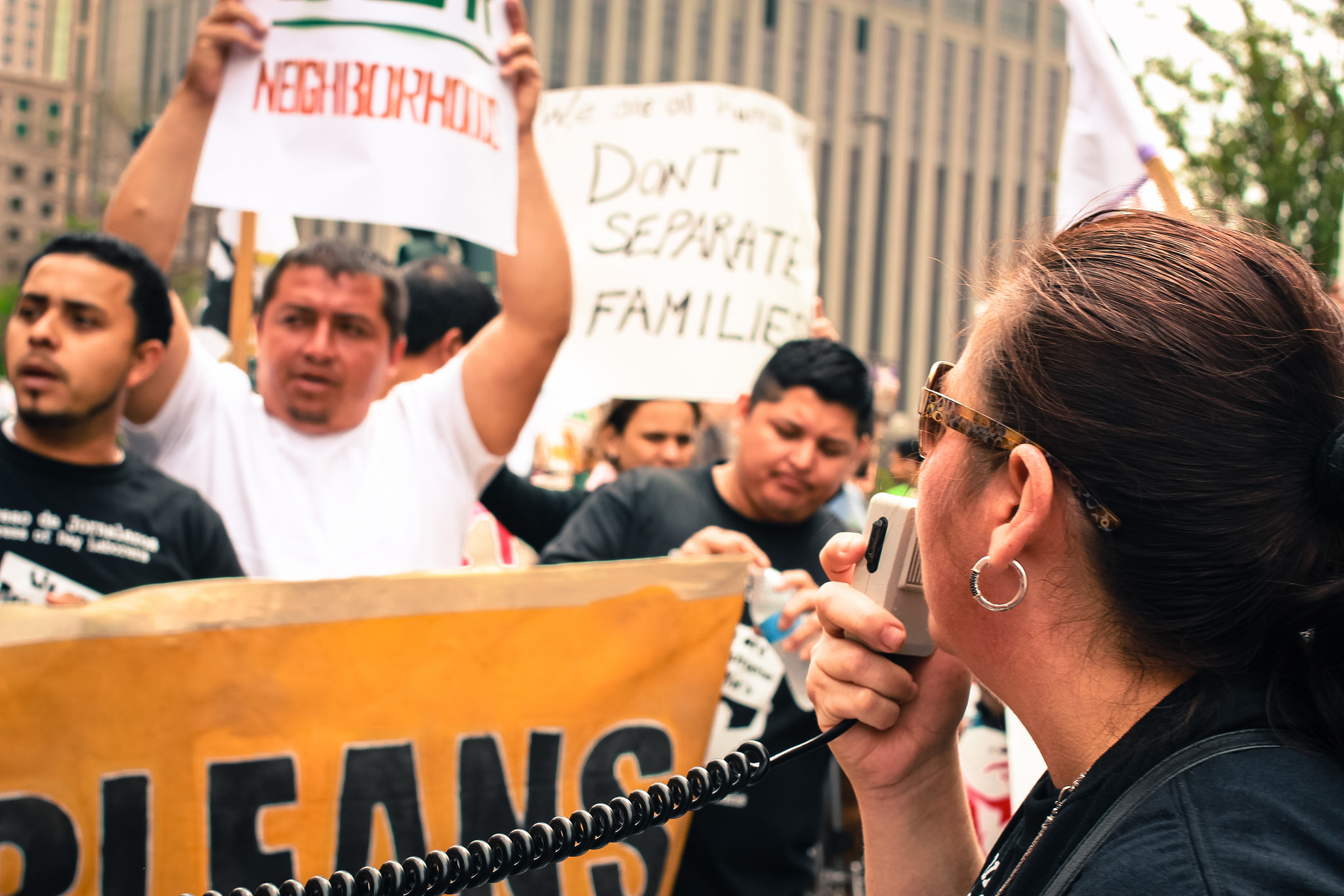 """Immigrant workers hold signs and banners while a person stands in foreground holding a microphone. One sign reads """"Don't separate families."""""""