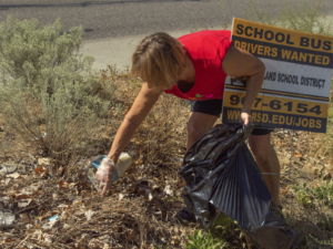 A red-shirt wearing worker stoops to pick up trash in a grassy area.