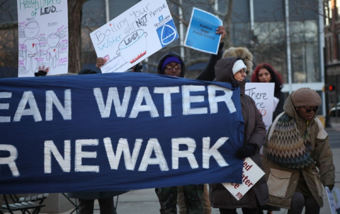 people hold a banner about clean water for Newark. Others hold hand made signs