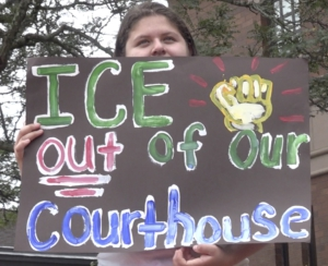 "An activist holds a black sign with colorful lettering that reads ""ICE out of out courthouses"". The sign partially obstructs their face."