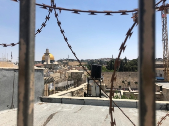 A view from a window with wire across it of Occupied East Jerusalem, overlooking the Dome of the Rock in Al-Aqsa.