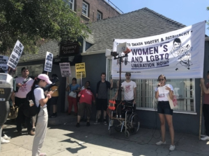 "A woman stands in front of a banner reading ""Women's and LGBTQ liberation now!"" She holds a mic. Others stand holding picket signs reading ""The system is sexist"" ""End the war on women's rights"" and ""Abortion is a right, defend Roe v. Wade."""