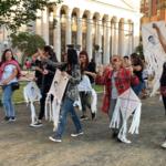 Protesters holding kites, chanting Ayotzinapa Vive! La Lucha Sigue!