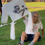 A man sits on the ground holding a kite depicting Mexican artist and activist Francesco Toledo, who died on September 5. Toledo started the international tradition of flying kites for the Ayotzinapa 43.