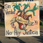 """A hand-made sign reads """"Sin Verdad No Hay Justicia"""", or """"Without truth, there is no justice."""""""