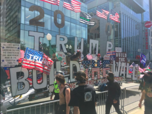 "A parade float decked with American flags reads ""trump 2020"" and ""build the wall"""