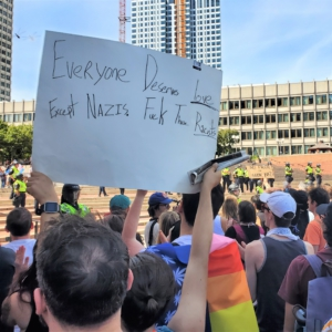 """A counter-demonstrator holds a sign that reads """"Everyone Deserves Love. Except nazis. F*ck those racists."""""""