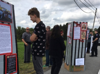 People stand on the roadside, looking at cardboard kiosks on which are placed images and typed text.