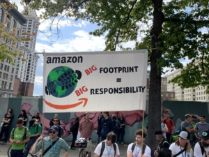 "People hold a banner while others stand nearby. Banner has image of a globe and the Amazon logo  and reads: ""Amazon, big footprint, big responsibility."""
