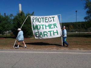 "activists hold a large banner that reads ""Protect Mother Earth."""