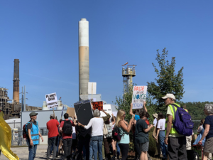 Activists holding signs rally in front of a smoke stack in Bow, New Hampshire.