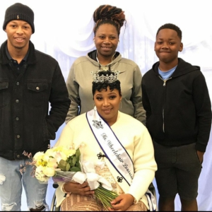 A woman sits in a wheelchair wearing a crown, Ms. Wheelchair Louisiana sash, holds a bouquet of flowers. Standing behind her are three members of her family.