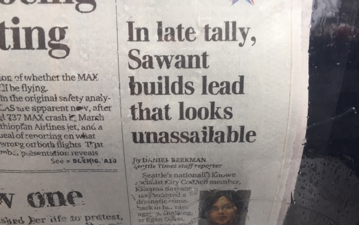 Rain-spattered newspaper box features headline on Sawant's growing lead, despite massive interference of Amazon. Liberation photo.